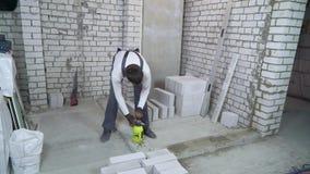 Lasso di tempo del muratore che moisturing base concreta con lo spruzzatore dell'acqua stock footage