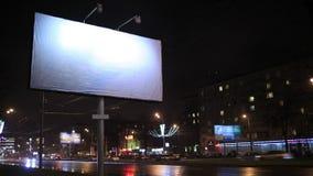 Lasso di tempo della scena urbana con un tabellone per le affissioni vuoto, di notte stock footage
