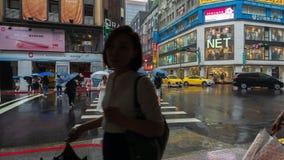 Lasso di tempo della via d'attraversamento della gente nel distretto di Ximen con la pioggia di caduta a Taipei, Taiwan stock footage