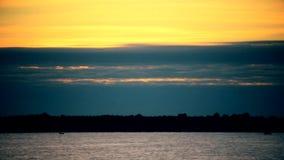 Lasso di tempo delle nuvole variopinte blu ed arancio all'alba sopra un fiume stock footage
