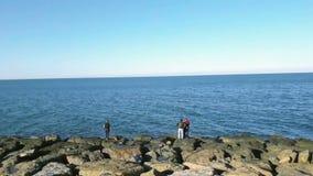 Lasso di tempo di grande gruppo di persone che pescano nella costa stock footage