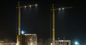 Lasso di tempo di vista di notte delle siluette di due gru che lavorano ad un cantiere di una costruzione multipiana nella notte  video d archivio