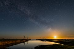 The moon shines on the harbour in Skärlöv, with Milky Way fading away stock images
