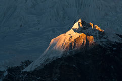Last beam on Cho Oyu slope. Sunset in Himalayas. Last beam on Cho Oyu slope - sixth highest mountain in the world Stock Photo