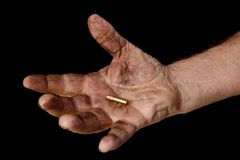 Last Bullet 1. A man's dirty hand holding a bullet Stock Photo