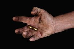 Last bullet 2. Man's hand holding a large bullet Royalty Free Stock Photos