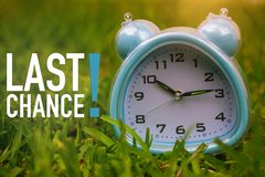 Last Chance, Business Concept - Text Showing Last Chance With A Clock On Grass Royalty Free Stock Photo