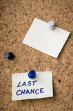Last chance. Message on sticker note pin on cork office board. Reminder sign written on card. Business concept stock photos