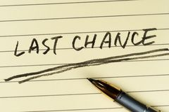Last chance words. Written on lined paper with a pen on it stock photography