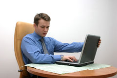 Last click and go home. Young specialist finishes his work on laptop royalty free stock photo