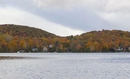 Last colors before winter. Overclouded scene of cottages around a lake mixed with the colorful trees of the mountain at fall stock photos