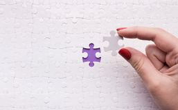 Hand putting last piece of puzzle on blue background. Last connecting piece jigsaw puzzle. Business connection, success and strategy concept, copy space stock image
