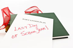 Last Day of School Year. Teacher's daily lesson plan sheet marked with Last Day of School placed with books and festive red ribbon Stock Photos