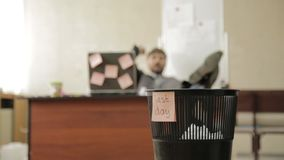 Last day at work, businessman in office throws papers in trash can, dreams of vacation.  stock footage