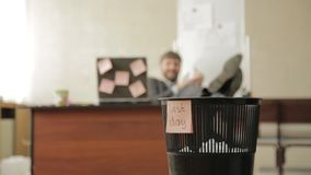 Last day at work, businessman in office throws papers in trash can, dreams of vacation.  stock video