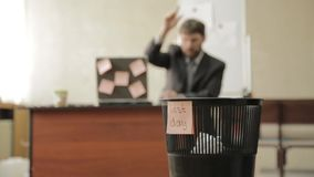 Last day at work, businessman in office throws papers in trash can, dreams of vacation.  stock video footage
