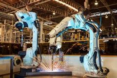 Last de team industriële robots het deel van het assemblagestaal in autofabriek royalty-vrije stock afbeelding