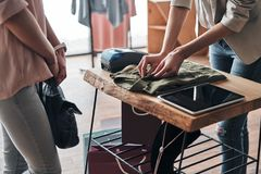 Last details. Close up of young woman folding a shirt for her cu. Last details. Close up of young women folding a shirt for her customer while working in the royalty free stock image