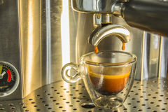 The last drops of strong espresso coffee being drawn from a espr Stock Image