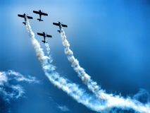 Last flight of four piston propeller aerobatic aicraft. Formation of four aerobatic aircraft during display. Grey scale photo. Clear blue sky in the background stock photo