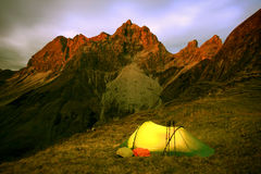 Last glow of daylight and an illuminated tent. Last glow of daylight hits the mountain peaks. The warm and illuminated tent promises a comfortable night Stock Photo