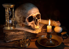 Last hour. Vintage skull on antique book with candle and hourglass stock photos