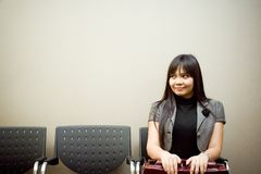 Last job seeker in waiting list. Asian businesswoman sitting alone in a waiting room for an appointment Stock Image