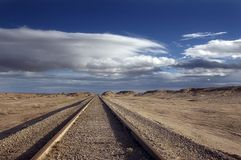 The Last Journey. A Lonely and Isolated Railroad Track Vanishes Under Clouds Stock Photos
