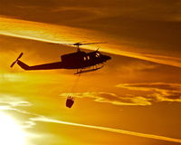 Last Light. Fire attack helicopter dropping water on range fire at sunset. Smoke, firefighter, sagebrush,orange,silhouette Stock Photography