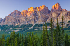 Last light hits the mountain tops. The sun sets in a peaceful mountain location Stock Image
