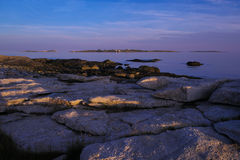 Last light of sunset on the rugged maine coast. The Glacier carved rocks at low tide at sunset on the Rugged and rocky Maine coast with the Rams Head Lighthouse Royalty Free Stock Photos