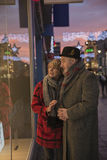 Last Minute Christmas Shopping. Mature couple are enjoying some winter shopping on an evening at christmas time Stock Images