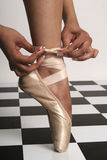 Last minute details. Ballerina tying the ribbon on her toe shoes royalty free stock images