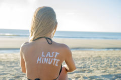 Last Minute Girl. Last Minute written with sunscreen on back of attractive woman sitting on beach looking at ocean royalty free stock photography