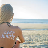 Last Minute Girl. Last Minute written with sunscreen on back of attractive woman sitting on beach looking at ocean Stock Images