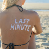 Last Minute Girl. Last Minute written with sunscreen on back of attractive woman sitting on beach looking at ocean royalty free stock image