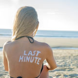 Last Minute Girl. Last Minute written with sunscreen on back of attractive woman sitting on beach looking at ocean Stock Image