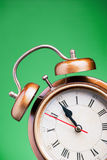 Last minute. A golden and white clock on the green background Stock Image