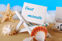 Last minute holidays. White board with text last minute standing on wooden deckchair on the beach stock photo