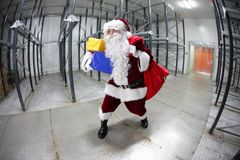 Last minute Santa Claus leaving empty storehouse. With red sack full of gifts Royalty Free Stock Image