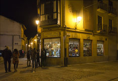 Last Minute Shopping. ZAMORA, SPAIN - DECEMBER 25, 2012: Last minute shoppers on Christmas Day before the lighted windows of a shop in the old city of Zamora Stock Photography