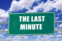 The last minute. Sign on the green board with clouds in background Stock Photos