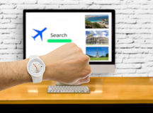 Last minute to fly. Hand with wristwatch with travel web in the background as the concept of last minute to buy tickets royalty free stock images