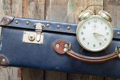 Last minute travel concept with old retro suitcase and alarm clock Royalty Free Stock Photos