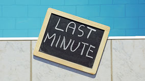 Last minute. Written on a chalkboard at a pool royalty free illustration