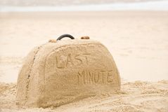 Suitcase made out of sand with writing. Last minute written on suitcase build out of sand on beach concept Stock Photography