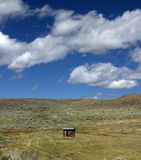 The last outhouse. An outhouse (toilet) stands in the middle of a field in the middle of nowhere on a ranch on Montana Royalty Free Stock Image