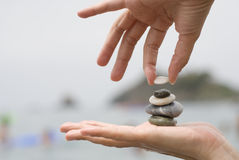 The last pebble. One hand holds stones in balance Royalty Free Stock Images