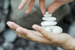 The last pebble. One hand holds stones in balance Royalty Free Stock Photography