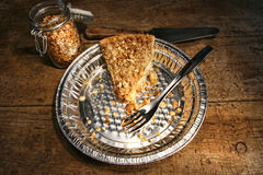 Last piece of apple crumble pie in aluminum  plate. On wood Royalty Free Stock Photos